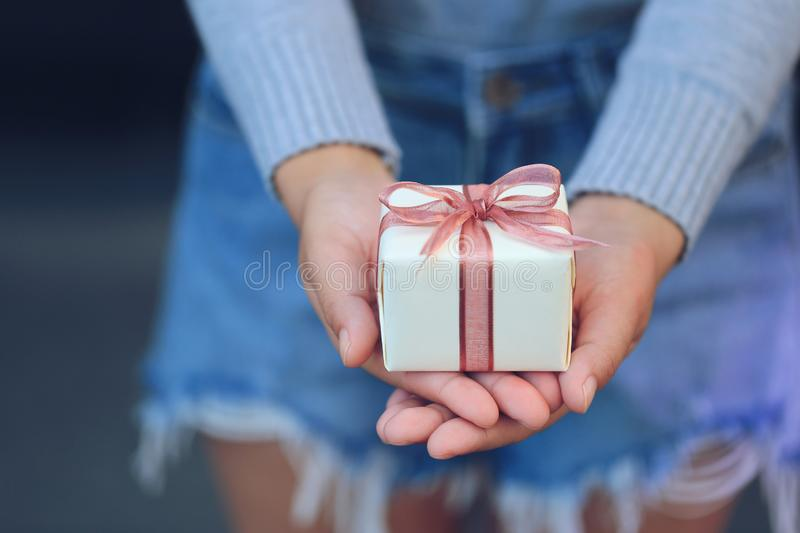 Selective focus of Woman hands holding yellow gift box with pink royalty free stock images