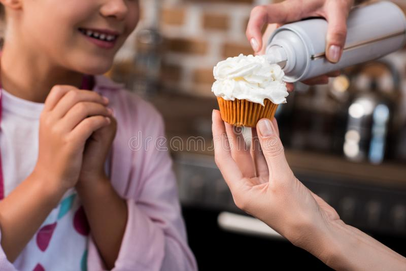 selective focus of woman putting buttercream on cupcake while daughter standing stock photography