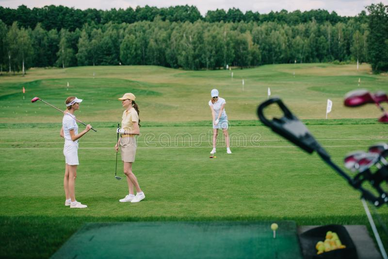 Selective focus of women in caps with golf equipment. At golf course royalty free stock photo