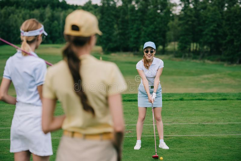 Selective focus of women in caps with golf equipment looking at friend playing golf. At golf course stock images