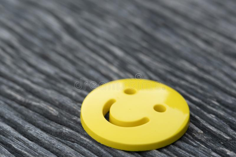 Selective focus of yellow emoticon smiley face icon symbol on vintage dark wooden table background. With copy space, for a positive mindset in business stock photography