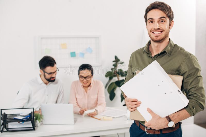 Selective focus of young manager standing with folders. In office royalty free stock image
