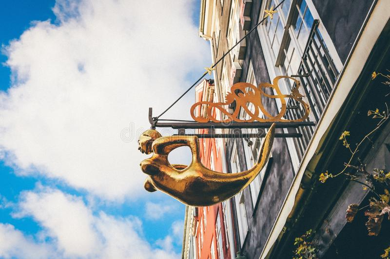 Selective low angle closeup shot of a gold mermaid statuette hanged from a holder on a building royalty free stock images