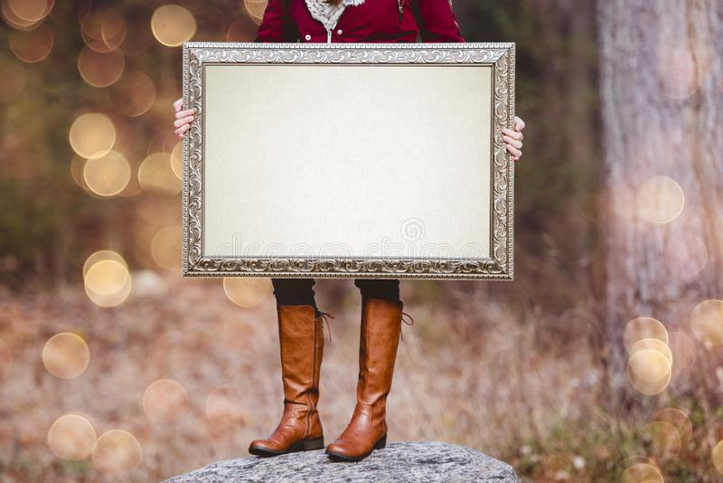 Selective shot of a person holding a blank picture frame as a space for your text. A selective shot of a person holding a blank picture frame as a space for your royalty free stock image