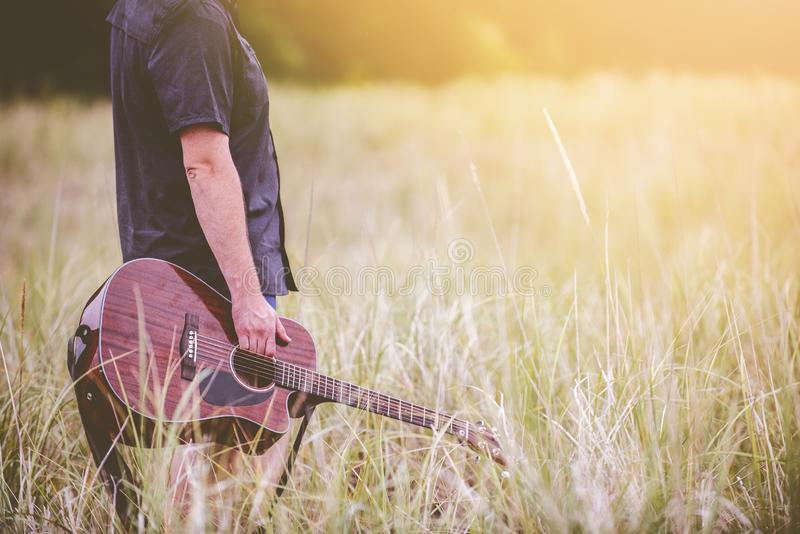 Selective shot of a person holding a brown acoustic guitar standing in the middle of grass field. A selective shot of a person holding a brown acoustic guitar royalty free stock photo