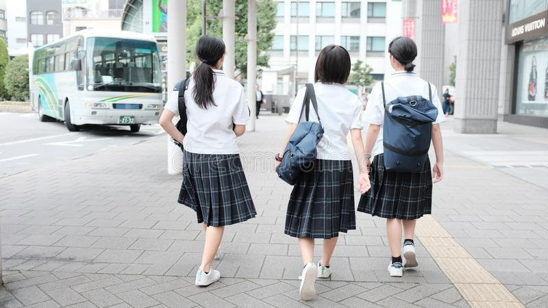 Selective shot of three schoolgirls wearing uniform and backpacks walking to the school-bus royalty free stock images