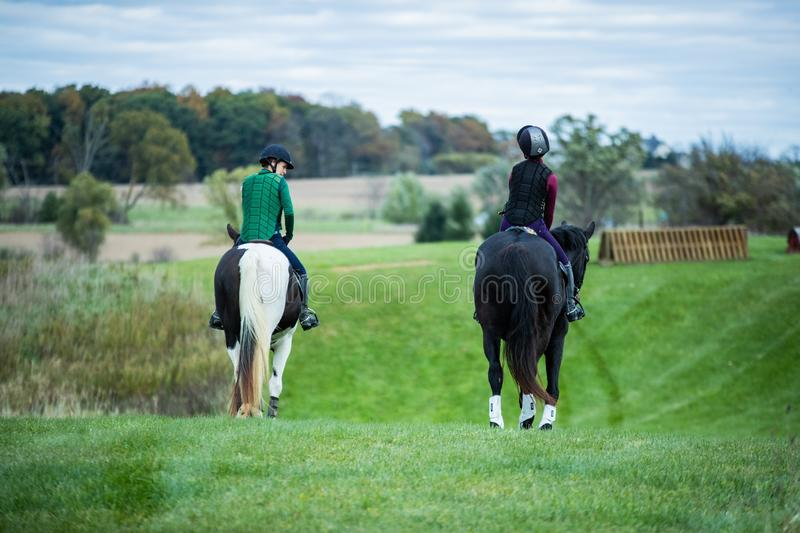 Selective shot of two people wearing horse riding vests riding on horses with black and white tails stock photos