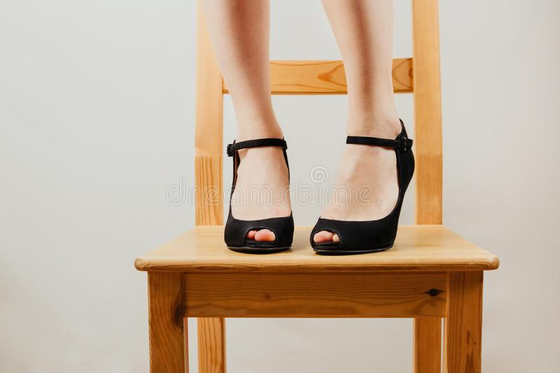 Selective shot of white woman`s legs in black high heeled shoes standing on a wooden chair. stock images