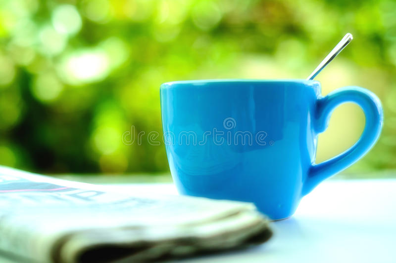 Selective and soft focus of blue coffee cup with blurred newspaper. And natural green background stock image