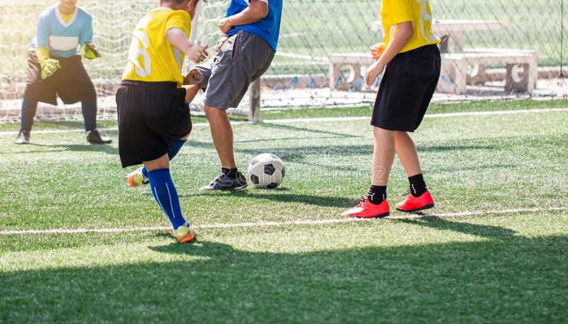 Selective to kid soccer player and coach are training and fighting to shoot ball and charges kid goalkeeper. Asian boy soccer player in football academy royalty free stock images