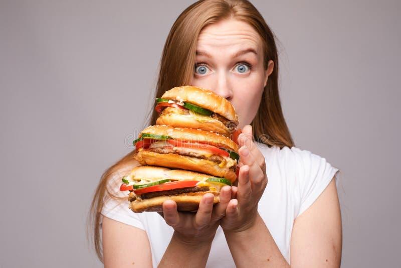 Selekcyjna ostro?? duzi smakowici hamburgery w r?kach zadziwiaj?ca dziewczyna zdjęcie stock