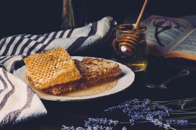 selekcyjna ostrość honeycombs na półkowej lawendzie i słoju z miodowym kijem zdjęcie stock