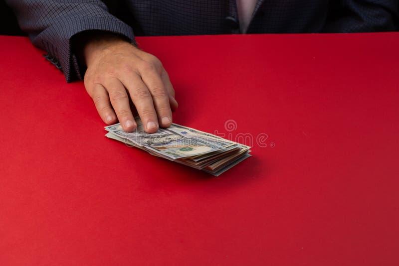 Selekcyjna ostrość, mężczyzna oferuje wsad sto dolarowych rachunków - ręce do góry Przekupność, łapówka, korupci pojęcie ręka dać fotografia royalty free