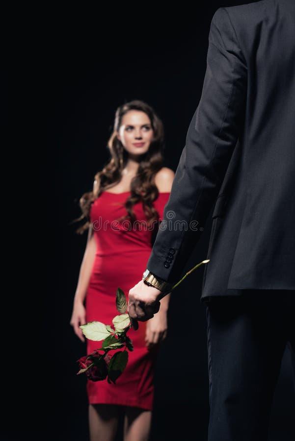 selekcyjna ostrość mężczyzny mienie wzrastał z kobietą w czerwieni sukni na tle odizolowywającym obrazy royalty free