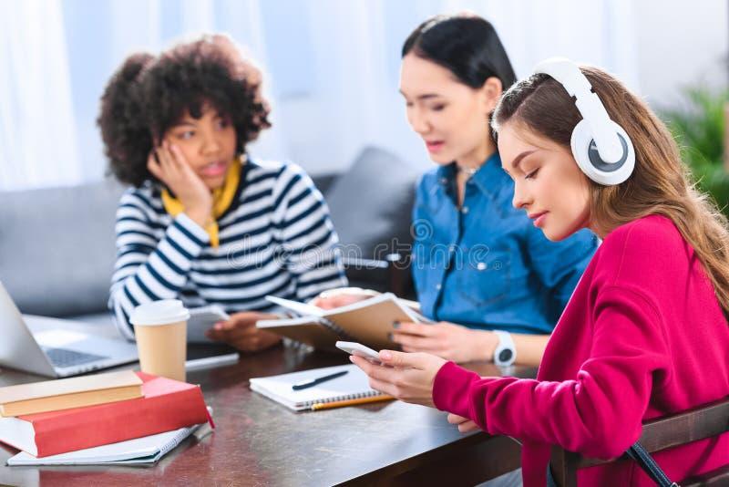 selekcyjna ostrość młody uczeń w hełmofonach używać smartphone z wieloetnicznymi przyjaciółmi obraz royalty free