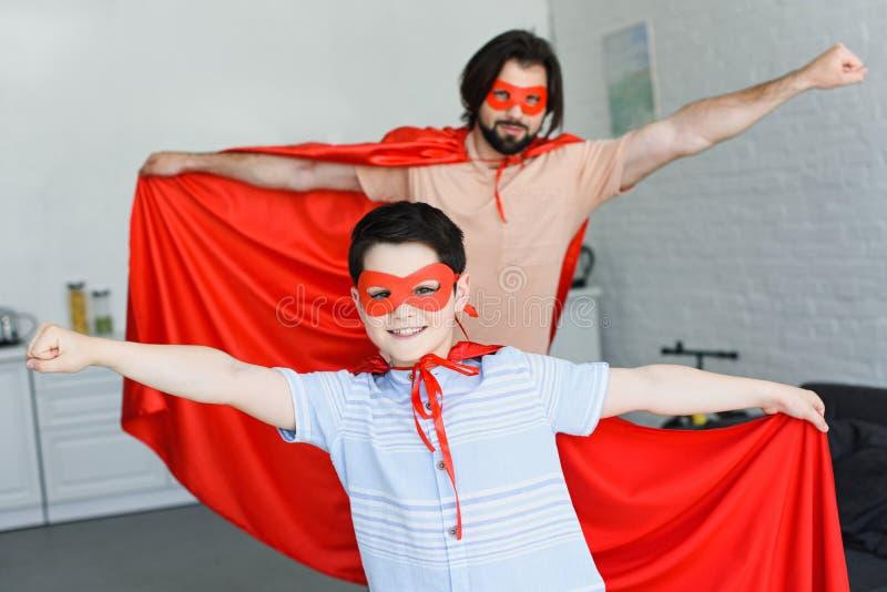 selekcyjna ostrość mały syn i ojciec w czerwonych bohaterów kostiumach obrazy stock