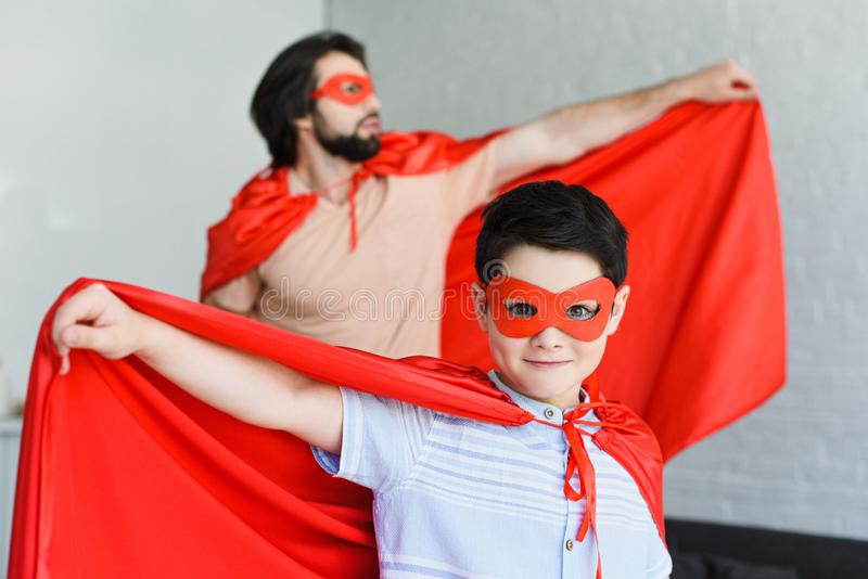 selekcyjna ostrość mały syn i ojciec w czerwonych bohaterów kostiumach obrazy royalty free