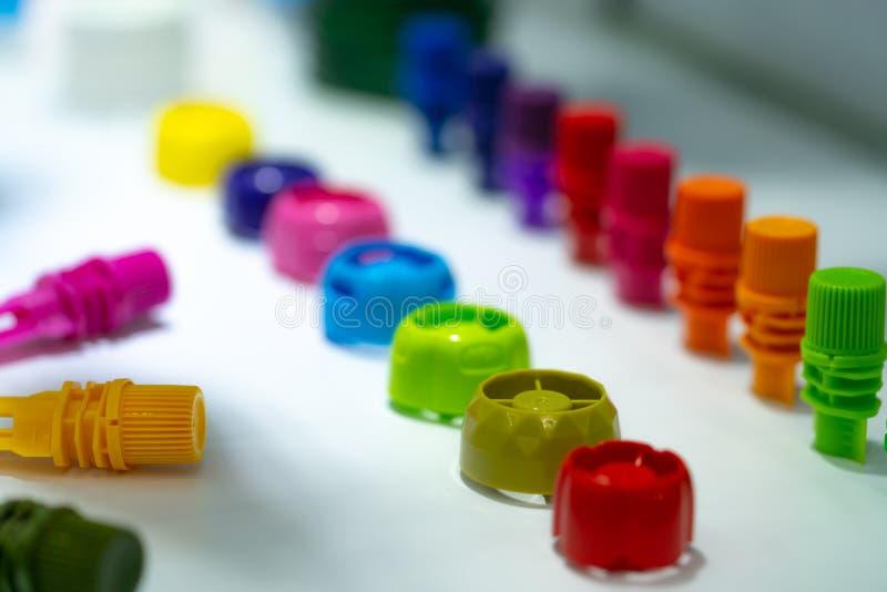 Selekcyjna ostrość na różnym typ plastikowa butelki nakrętka karmowy i napój produkt Zieleń, kolor żółty, czerwień, menchia, poma zdjęcia royalty free