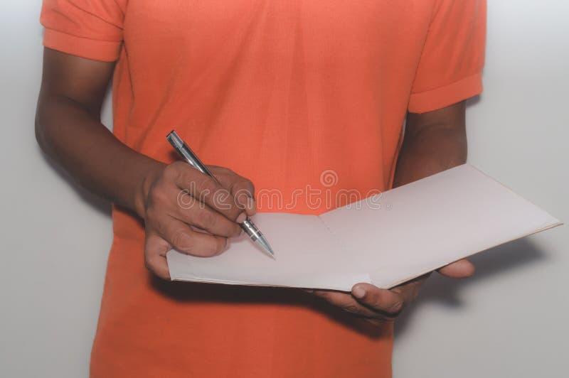 Selekcyjna ostrość na ręce pisze z piórem, notatnik zdjęcie stock