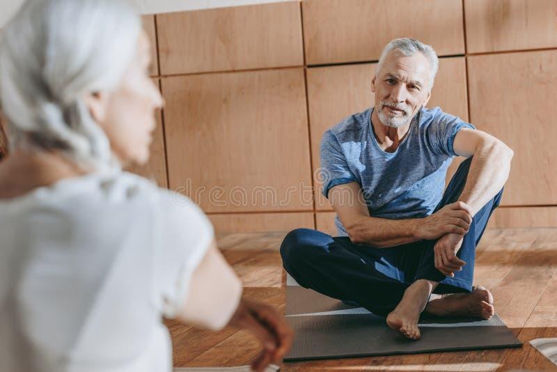 selekcyjna ostrość na starszych ludziach w sportswear obsiadaniu na joga matuje obraz stock