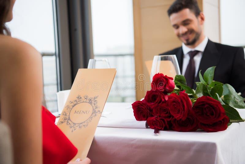 selekcyjna ostrość para czytelniczy menu na romantycznej dacie w restauraci na st zdjęcie stock