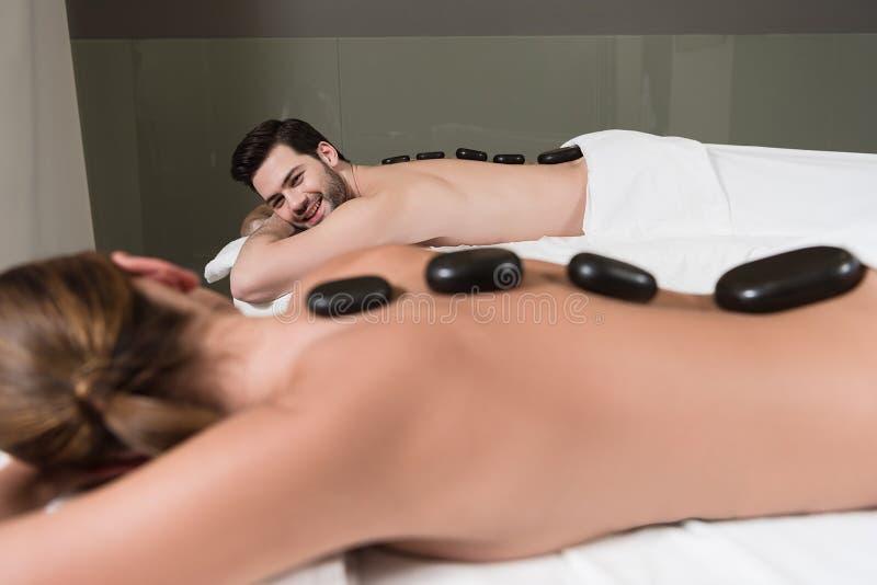 selekcyjna ostrość patrzeje each inny para podczas gdy mieć gorącego kamienia masaż w zdroju fotografia royalty free