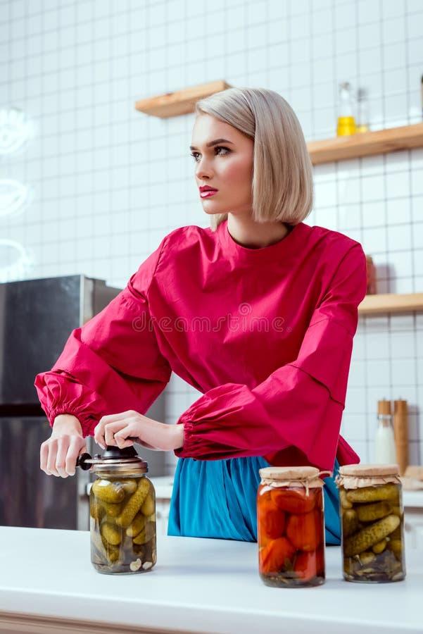selekcyjna ostrość piękny elegancki gospodyni domowej lakowania słój kiszeni ogórki zdjęcie stock