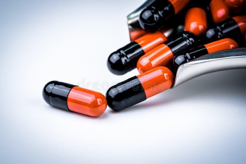 Selekcyjna ostrość pomarańczowe i czarne kapsuł pigułki na stal nierdzewna leka tacy Antybiotyka opór globalna opieka zdrowotna fotografia royalty free