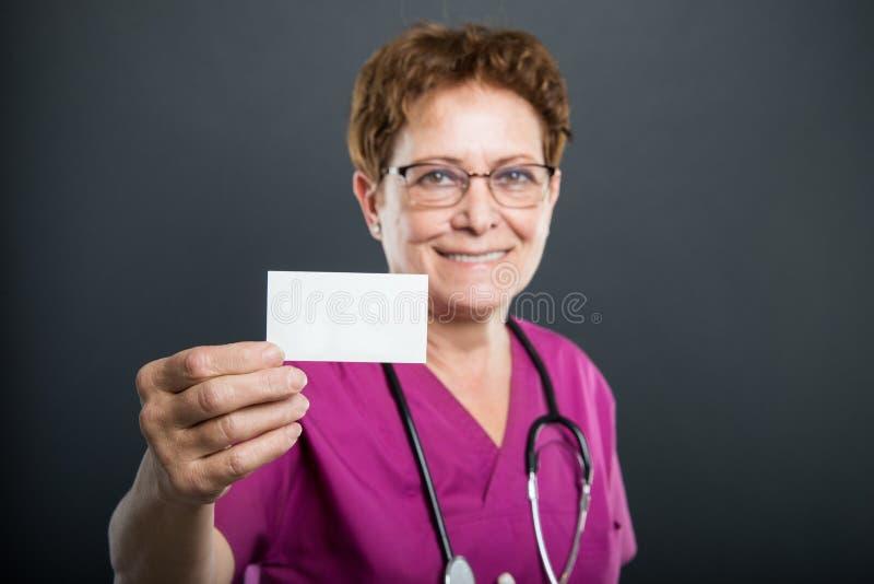 Selekcyjna ostrość starszej damy doktorska pokazuje wizytówka obraz stock