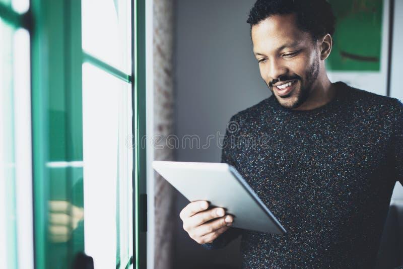 Selekcyjna ostrość Uśmiechniętego brodatego Afrykańskiego mężczyzna czytelnicza książka na cyfrowej pastylce podczas gdy stojący  fotografia royalty free