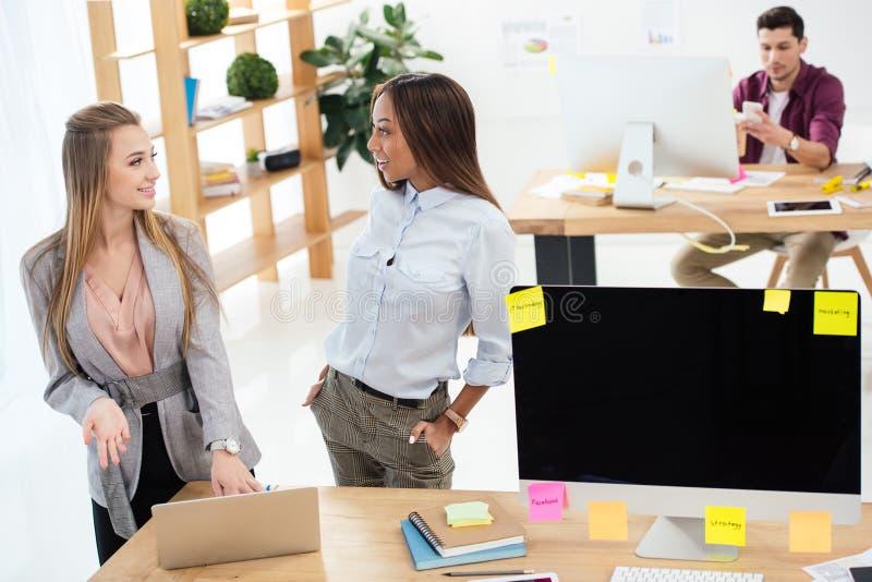 selekcyjna ostrość wielokulturowi bizneswomany używa laptop wpólnie przy miejsce pracy zdjęcie royalty free