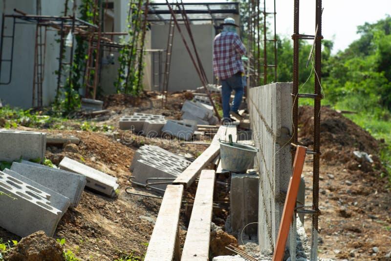 Selekcyjna ostrość wzmacnienie stalowa i cementowa cegły ściana z zamazanymi pracownikami w tle przy budową obrazy royalty free