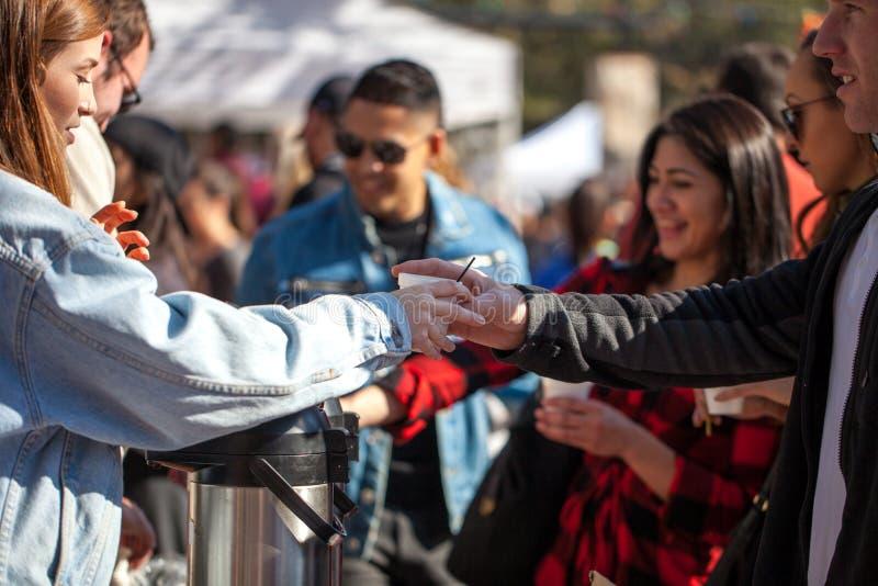 SELEKCYJNA ostrość z akcentem na rękach i filiżance ludzie dostaje kawę podczas 2018 Coffe San Antonio, TEKSAS, STYCZEŃ - 6, 2018 zdjęcie royalty free