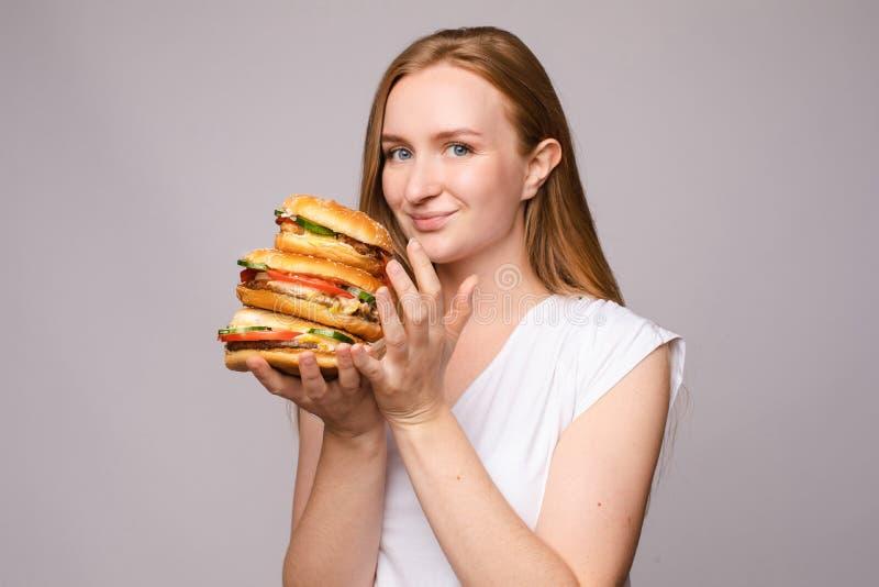 Selekcyjna ostro?? duzi smakowici hamburgery w r?kach zadziwiaj?ca dziewczyna zdjęcia royalty free