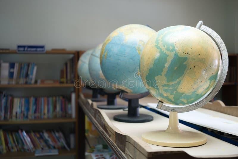 Selekcyjnej ostrości kuli ziemskiej wzorcowa symulacja z półka na książki tłem obrazy stock