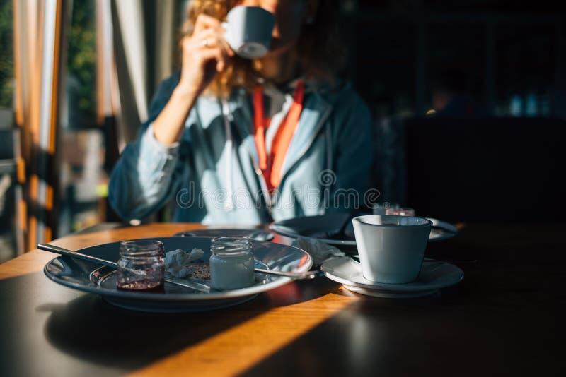 Selekcyjnej ostrości resztki deser na stole i dziewczynie pije kawę na tle Młoda kobieta indoors skończona jedzący tort i obraz stock