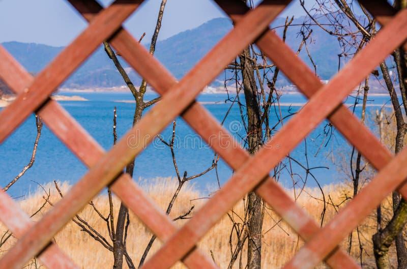 Selekcyjny zamazuje kratownicy pracy ogrodzenie z jeziorem i drzewa w foc fotografia stock