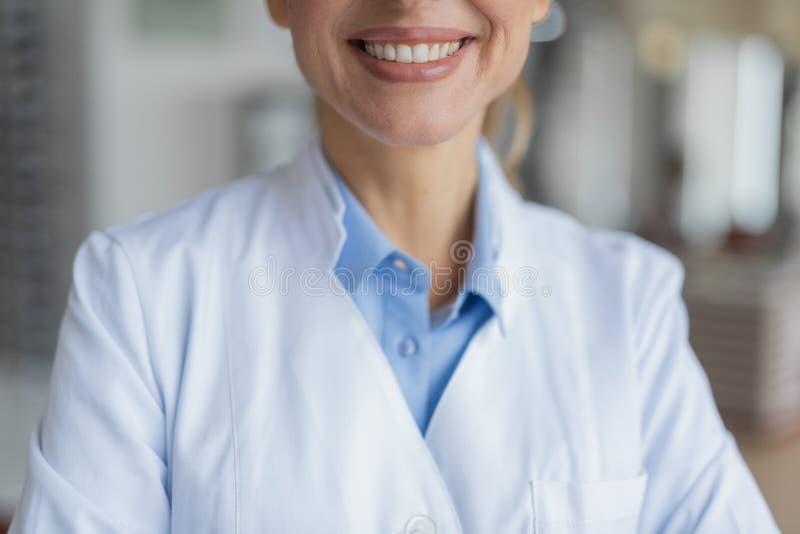 Selektiv fokus av angenämt kvinnligt le för doktor arkivfoto