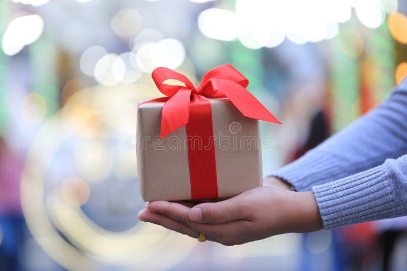 Selektiv fokus av asken för gåva för kvinnahandinnehav med det röda bandet för jul- och nyårsdagen- eller hälsasäsong royaltyfri bild