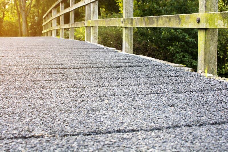Selektiv fokus av cementbron med träkuggegångbanan along till skogen arkivbilder