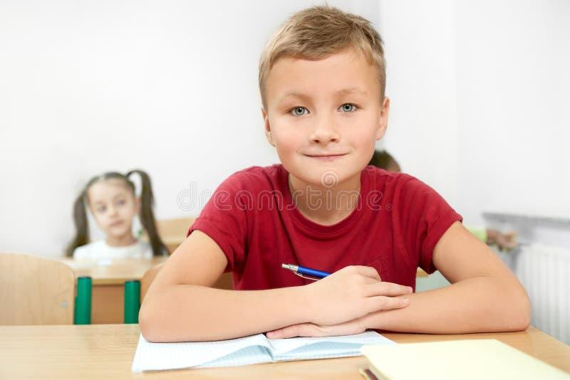 Selektiv fokus av den gladlynta pojken som sitter på skrivbordet i klassrum royaltyfri fotografi