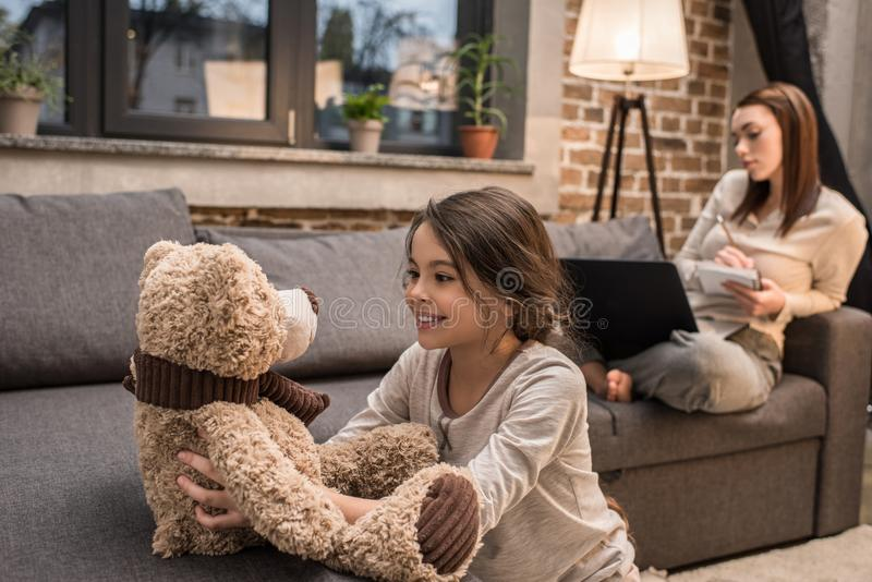 selektiv fokus av den gladlynta ungen som spelar med nallebjörnen medan moder som arbetar på bärbara datorn på soffan arkivbilder