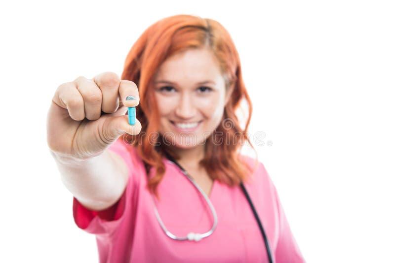 Selektiv fokus av den unga kvinnliga preventivpilleren för doktorsvisningblått royaltyfri fotografi