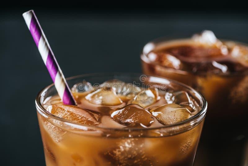 selektiv fokus av exponeringsglas av kallt med is kaffe med sugrör på mörk bakgrund royaltyfria foton