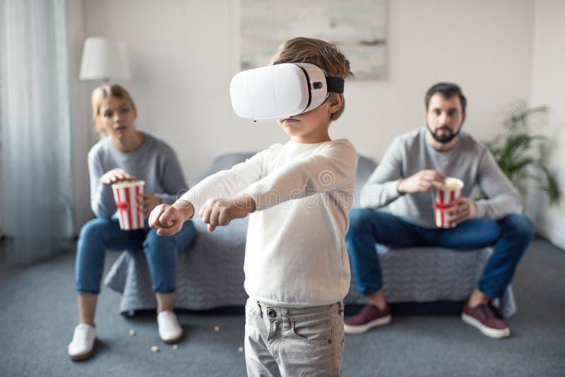 selektiv fokus av föräldrar med popcorn som ser ungen som spelar i vrhörlurar med mikrofon royaltyfri fotografi