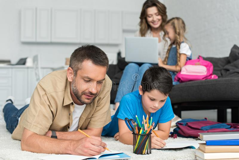 selektiv fokus av fadern och sonen som tillsammans gör läxa medan moder och dotter som använder bärbara datorn på soffan arkivbild