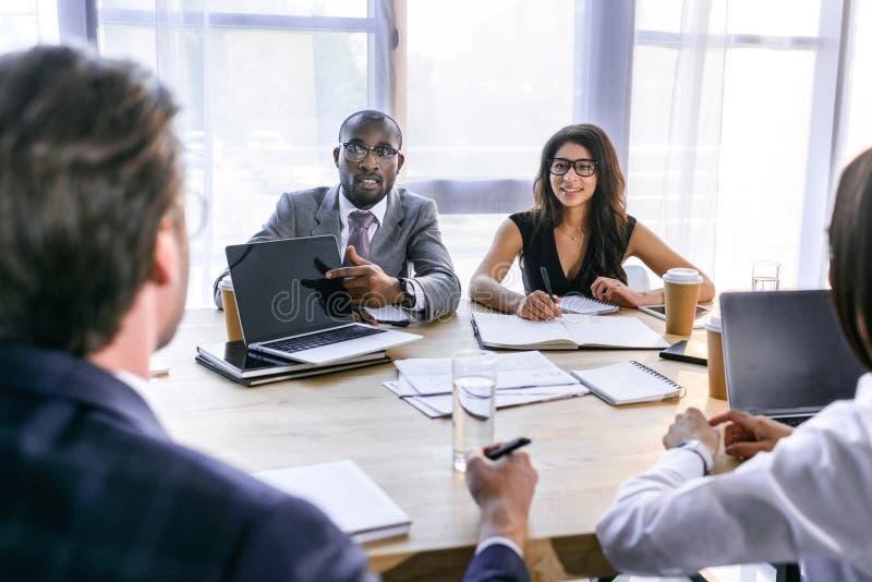 selektiv fokus av gruppen av multietniska affärskollegor som diskuterar strategi under affärsmöte royaltyfria bilder