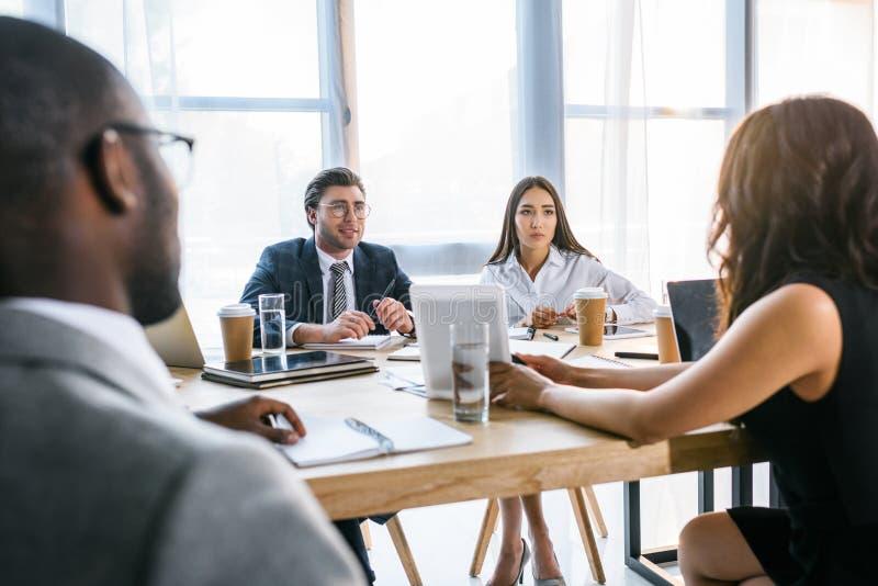 selektiv fokus av gruppen av multietniska affärskollegor som diskuterar strategi under affärsmöte royaltyfria foton