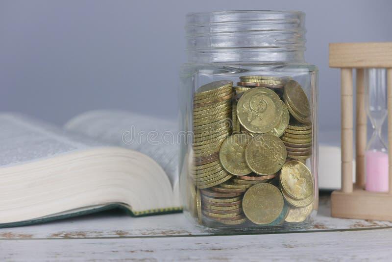 Selektiv fokus av guld- mynt på boken med timglas Finans- och utbildningsbegrepp royaltyfria foton