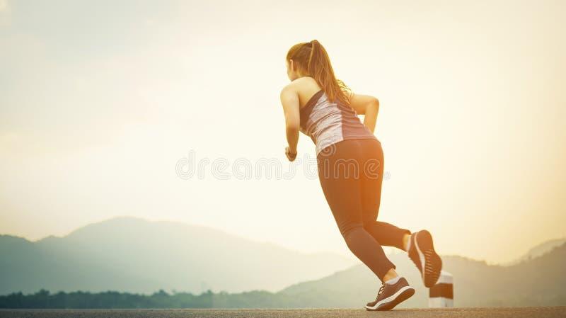 Selektiv fokus av löparen för ung kvinna på vägen på solnedgången Jogga genomk?rare och sunt livsstilbegrepp f?r sport royaltyfria foton